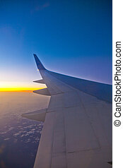 wing of aircraft in sunset