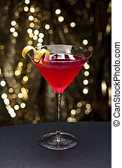 Cosmopolitan cocktail with lemon garnish in front of a gold...