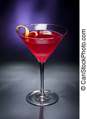 Cosmopolitan cocktail with lemon garnish in front of a black...