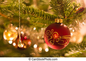 Decorated ball in christmas tree with other decoration and...