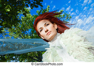 beautiful woman in white against blue sky and green trees -...