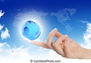 Globe in human hand against sun and blue sky