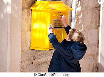 Boy sending letter - Boy puts letter into yellow postbox