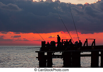 Fishermans on a pier in the evening on a sea