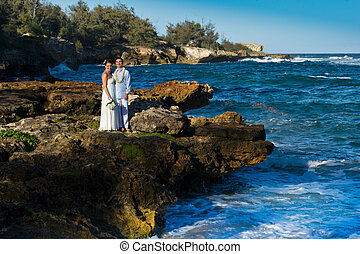 Just Married. Beautiful young couple on a rocky ocean shore.