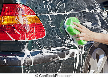 Washing car - Closeup image of a hand with a soapy sponge...