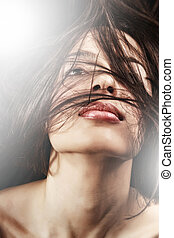 Woman with sensual lips and hair in motion