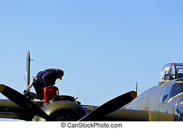 WWII Aircraft - A crewman fuels a nostalgic WWII aircraft at...