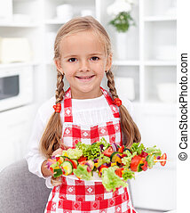 Happy girl with vegetables plate and apron - healthy eating