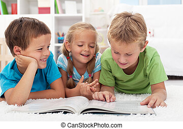 Kids having fun reading - Three kids having fun reading a...