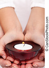 Child and adult hands holding candle