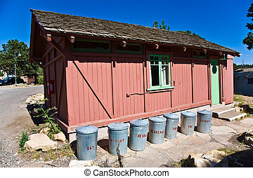 wooden house with litter boxes made of tin per weekday in...