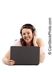 Happy young woman lying on floor listening to music on her laptop over white background