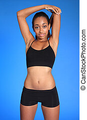 Fit body of African woman doing shoulder stretch