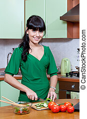 Beautiful woman cooking healthy food in the kitchen -...