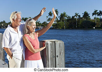 Happy Senior Couple Waving Outside in Sunshine by Sea -...
