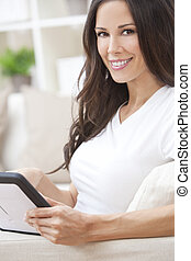 Young Brunette Woman Using Tablet Computer At Home on Sofa