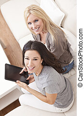 Two Young Women Using Tablet Computer At Home on Sofa