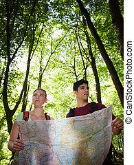 young couple looking at map during trek - young man and...