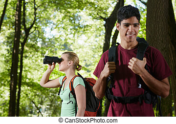 young man and woman hiking in forest with binoculars - young...