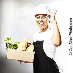 woman carrying food - portrait ofmiddle aged woman carrying...