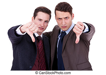 business men with thumb down gesture - two young business...