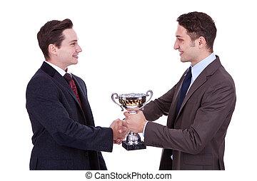 winning team - business man handing a trophy to his winning...