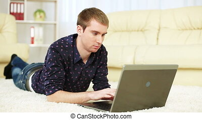 Guy lying on carpet with laptop