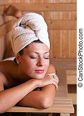 Woman relaxing in the sauna - Beautiful young woman relaxing...