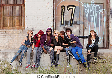 Young punk gang hanging out behind an abandoned urban...
