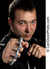 man with brass knuckles in black background