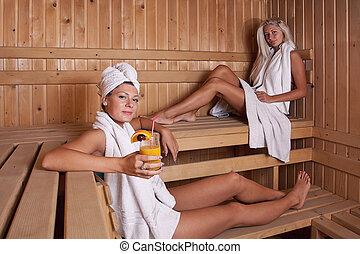 two women enjoying a hot sauna, having a casual chat