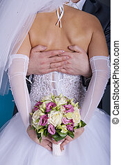 bridegroom embraces his bride, and she holds a bridal...