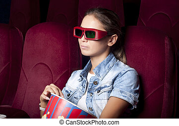 woman at the cinema - young woman sitting alone in the...