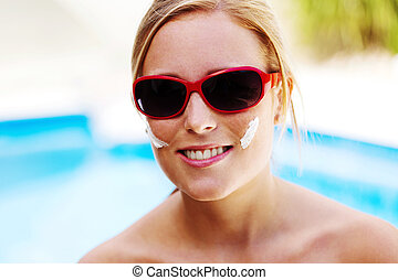 woman with sunglasses and sun cream - young woman with...