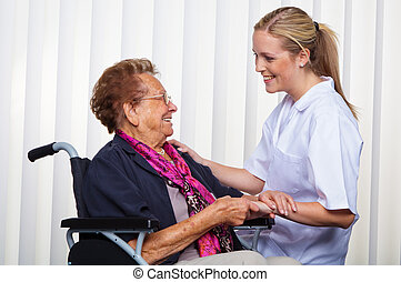 nurse and the old woman in a wheelchair - a nurse and an old...