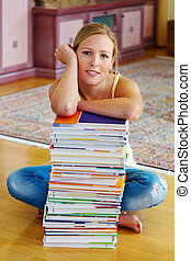 student with a stack of books and computers