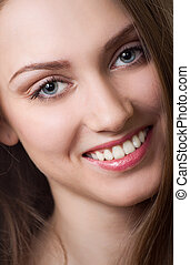 Beautiful young woman smiling. Isolated over white...