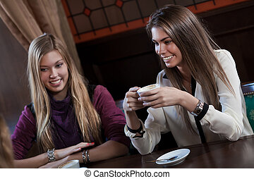 pretty girl-friends talk and drink coffee in cafe house
