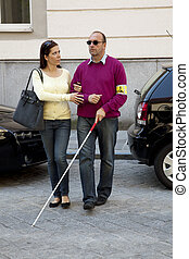 woman helps blind man - a young woman helps a blind man on...