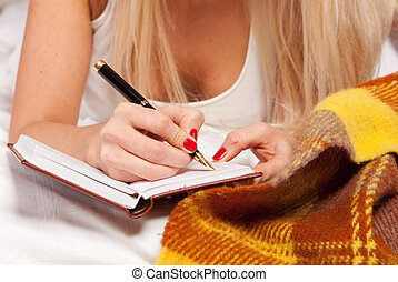 writing a diary while lying - Portrait of a sexy young woman...