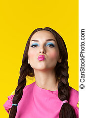 Beauty girl with funny make-up in doll costume on yellow...