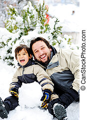 Father and son playing happily in snow making snowman,...