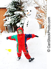 Kid playing happily in snow making snowman, winter season
