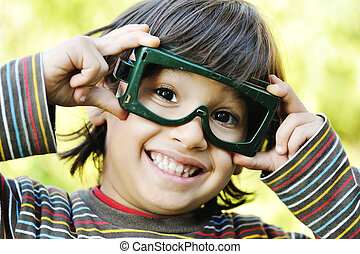 Very positive boy holding his big funny glasses and smiling, outdoor
