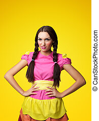 Funny girl in doll costume look serious on yellow background