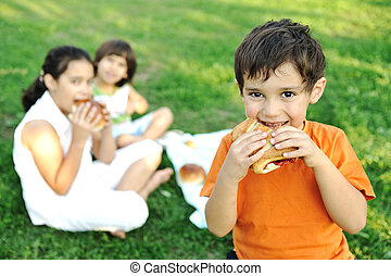 Small group of children in nature eating snacks together,...