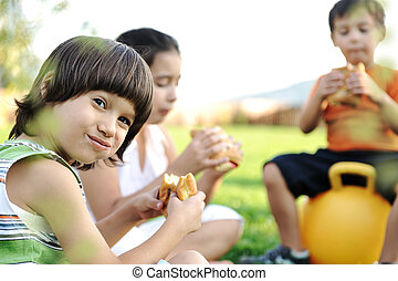 Three children in nature playing and eating together