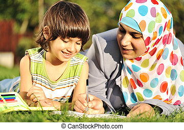 Muslim mother and her little son learning together laying on ground in nature, park, educational process