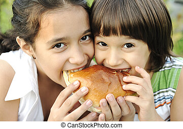 Closeup of two children eating sandwich in nature together,...